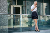 Smiling attractive blonde businesswoman with smartphone — Stock Photo