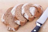 Homemade fresh baked bread and knife — Stock Photo