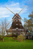 Traditional wooden windmill in a lush garden — Stock Photo