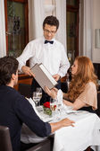 Waiter serving a couple in a restaurant — Foto de Stock