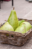 Fresh ripe pears in a wicker basket — Stock Photo