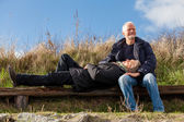 Happy senior couple relaxing together in the sunshine — Stock Photo