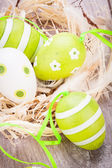 Green Easter eggs in straw — Stock Photo