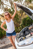 Blond woman inspecting car — Stock Photo