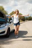 Woman hitchhiking at roadside — Stock Photo