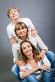 Three generations of attractive women in row — Stock Photo