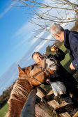 Elderly couple petting a horse — Stock Photo