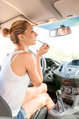 Woman applying makeup in the car — Stock Photo