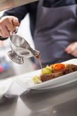 Chef plating up food in a restaurant — Stock Photo