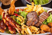 Platter of mixed meats, salad and French fries — Foto de Stock