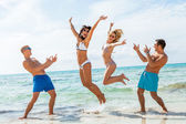 Friends jumping  on a beach — Stock Photo
