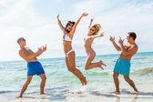 Amigos saltando en la playa — Foto de Stock