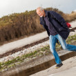 Elderly energetic man running along a beach — Stock Photo