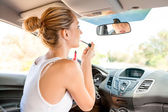 Attractive woman applying makeup in the car — Stock Photo