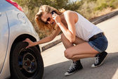Woman inspecting car wheels — Stock Photo