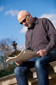 Bald man reading in sunglasses — Stock Photo