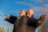 Elderly couple embracing and celebrating the sun — Stock Photo