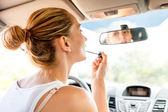 Beautiful woman applying makeup in the car — Stock Photo