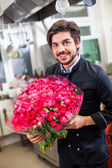 Smiling chef with flowers — Stock Photo
