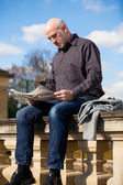 Bald man reading a newspaper — Stock Photo