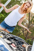 Woman inspecting car engine — Stock Photo