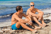 Two handsome young men chatting on a beach — Stock Photo
