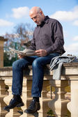 Man sitting reading a newspaper on a stone wall — Stock Photo