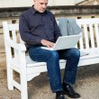 Man sitting on a bench using a laptop — Stock Photo #47010059