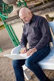Hombre sentado en un banco usando una laptop — Foto de Stock