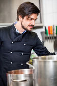 Chef stirring a huge pot of stew or casserole — Stock Photo