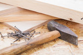 Mallet with nails and planks of new wood — Stock Photo