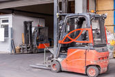 Small orange forklift parked at a warehouse — Stock Photo