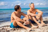 Men chatting on a beach — Stock Photo