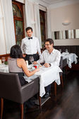 Waiter  accommodating couple — Stock Photo