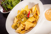Nachos with cheese sauce — Stock Photo