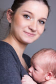 Young mother carrying infant — Stockfoto