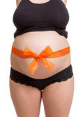 Pregnant woman wearing a bow on her belly — Stock Photo