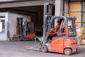 Small orange forklift parked at a warehouse — Foto Stock