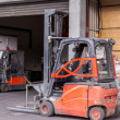 Постер, плакат: Small forklift parked at warehouse