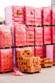 Red clay bricks stacked on pallets — Stok fotoğraf