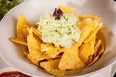 Crisp corn nachos with guacamole sauce — Stock Photo