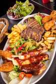 Platter of mixed meats, salad and French fries — Стоковое фото
