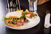Delicious pastrami club sandwich and pickles — Stock Photo