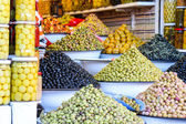 Olives and pickles on display at a farmers market — Stock fotografie