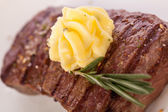 Grilled beef steak topped with butter and rosemary — Stock Photo