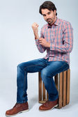 Handsome young man sitting on a wooden box — Stock Photo