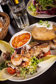 Grilled prawns with endive salad and jacket potato — Stock Photo