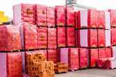 Red clay bricks stacked on pallets — Stock Photo
