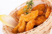 Crumbed chicken nuggets in a basket — 图库照片