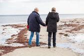 Senior couple walking on beach — Stock Photo